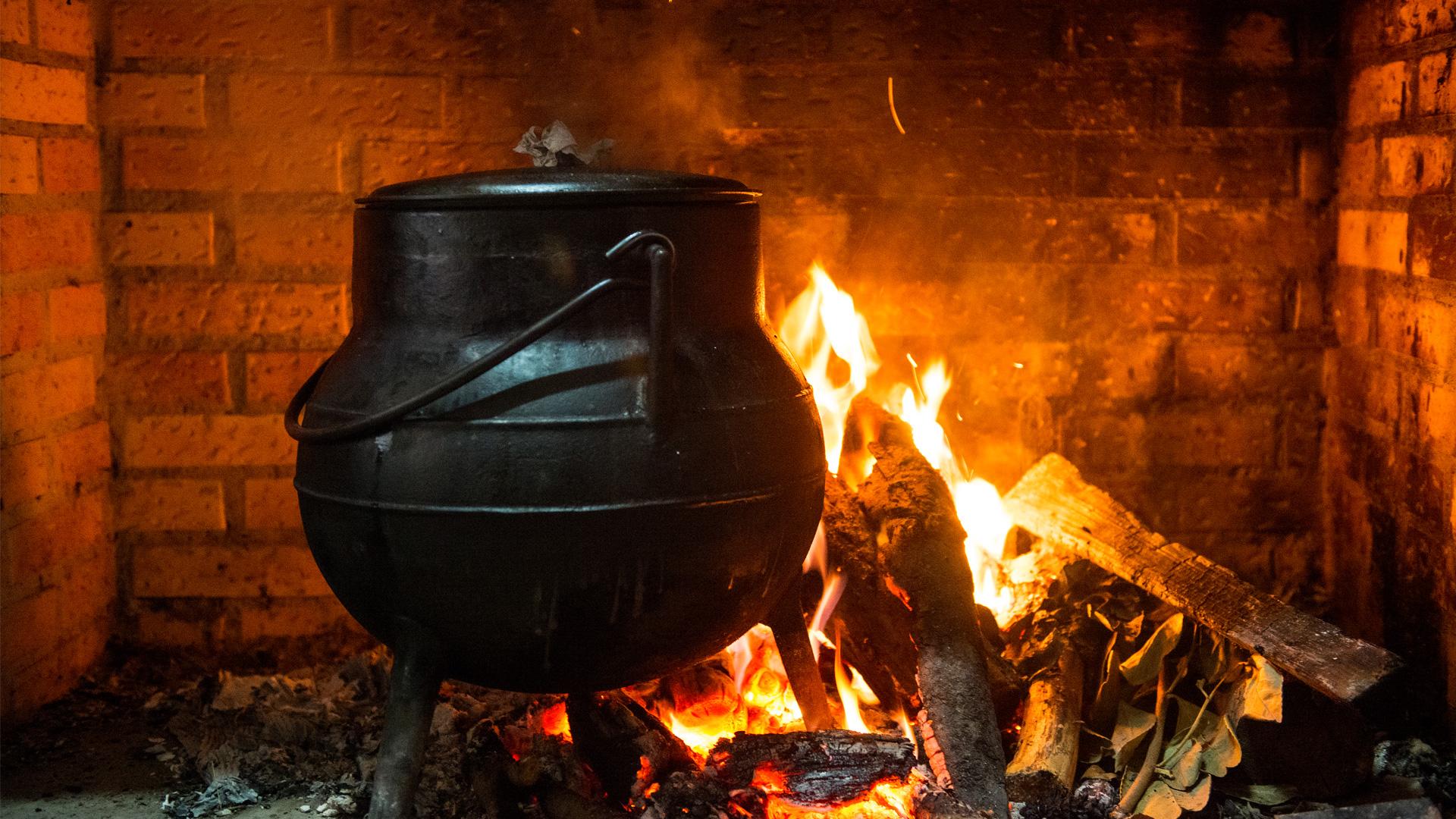 Pote de ferro com três pés, ao lume num fogo aceso.
