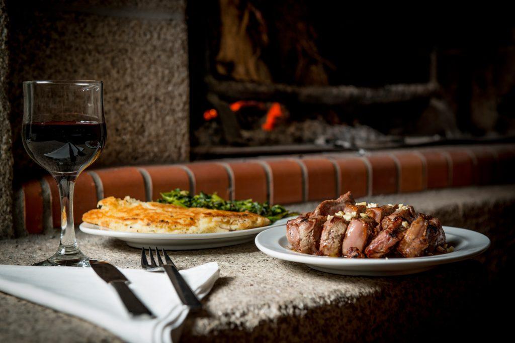 Prato típico de carne na Casa Ti João: uma posta barrosã acompanhado por um copo de vinho tinto e talheres.