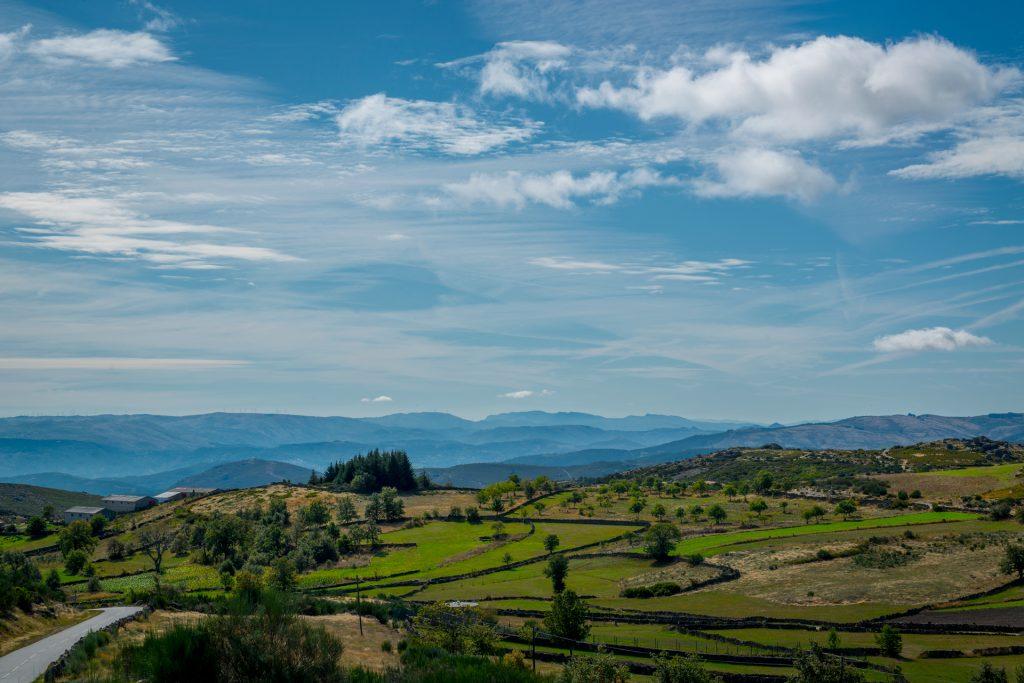 Paisagem com várias montanhas em fundo, em Coutos de Dornelas, em segundo plano lameiros, ladeados com muros de pedra.