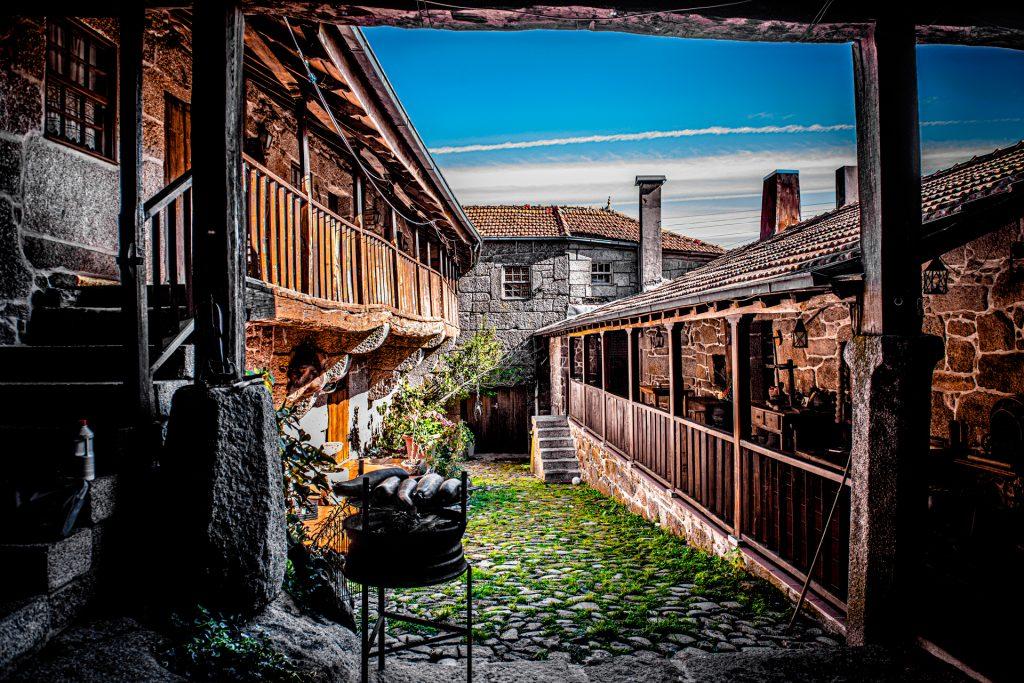 Pequeno grelhador no pátio da Casa do Pedro. Duas varandas de madeira, uma de cada lado, e uma casa de pedra ao fundo.
