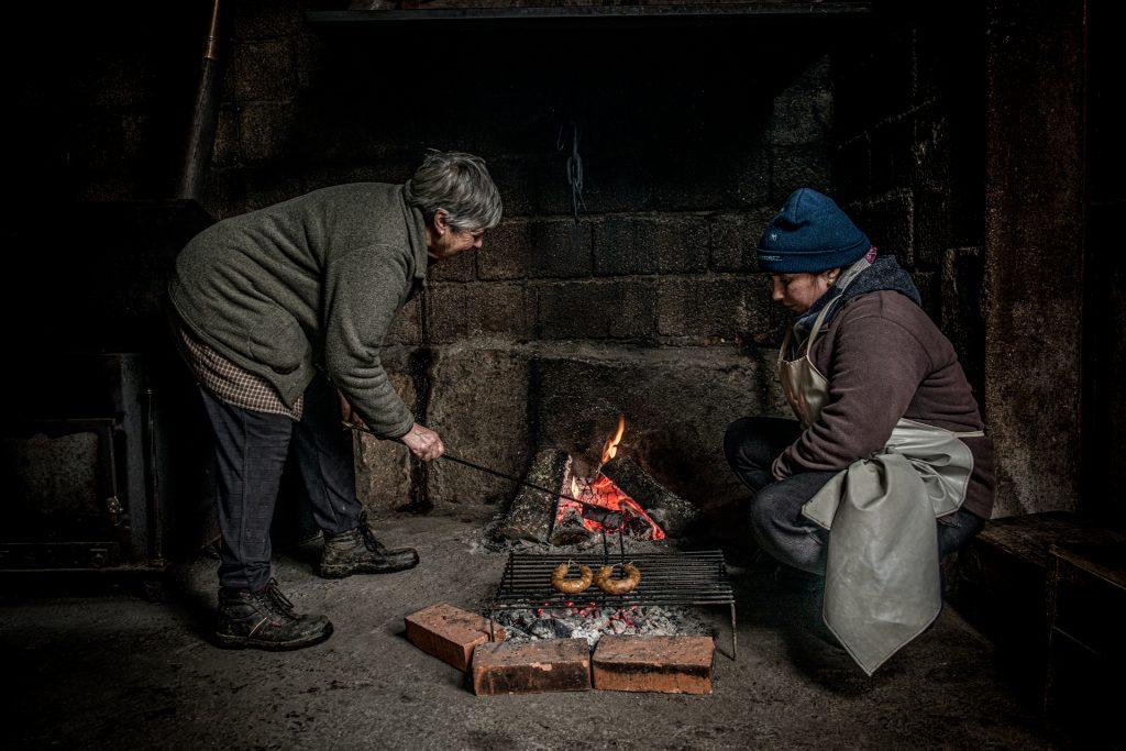 Em Alturas do Barroso, duas mulheres assam duas alheiras numa fogueira no chão.