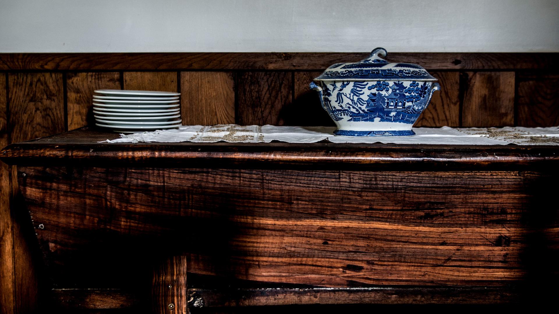 Amassadeira em madeira, sobre a qual está um naperon de linho, e a meio uma terrina em louça branca e azul.