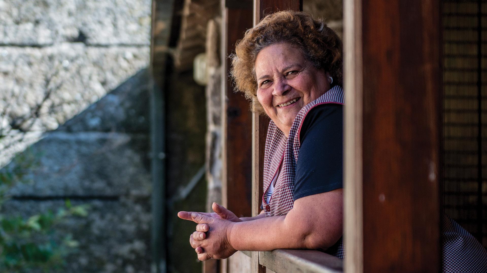 A anfitriã da Casa do Pedro olha sorridente para o fotógrafo.