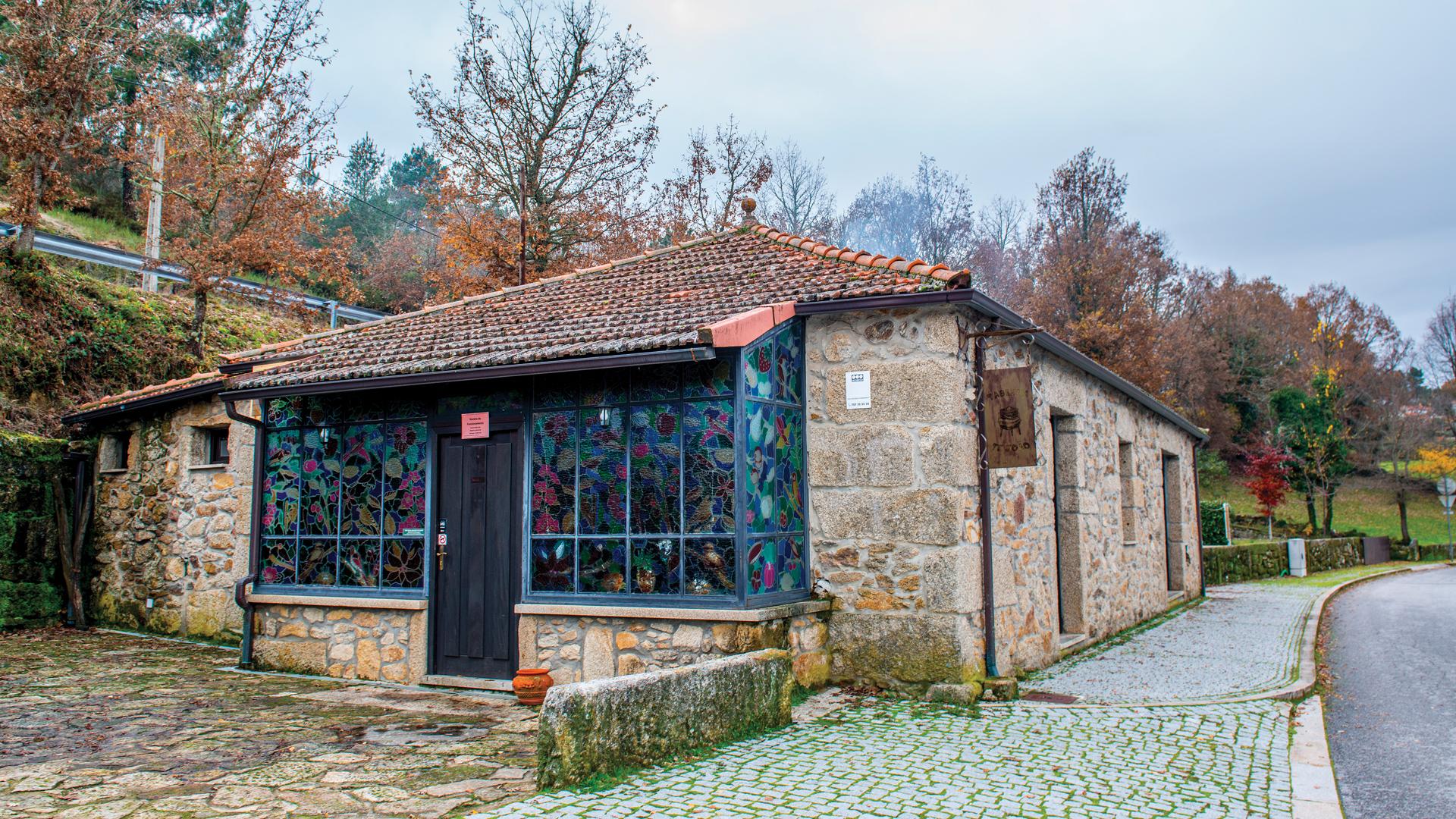 Exterior e entrada da Casa Ti João. Casa de pedra e entrada com vitrais coloridos.
