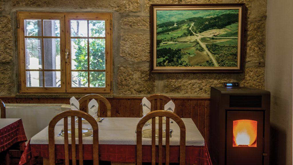 Detalhe do interior da Casa de Vilar, com paredes de pedra, janelas de madeira, mesas e cadeiras.