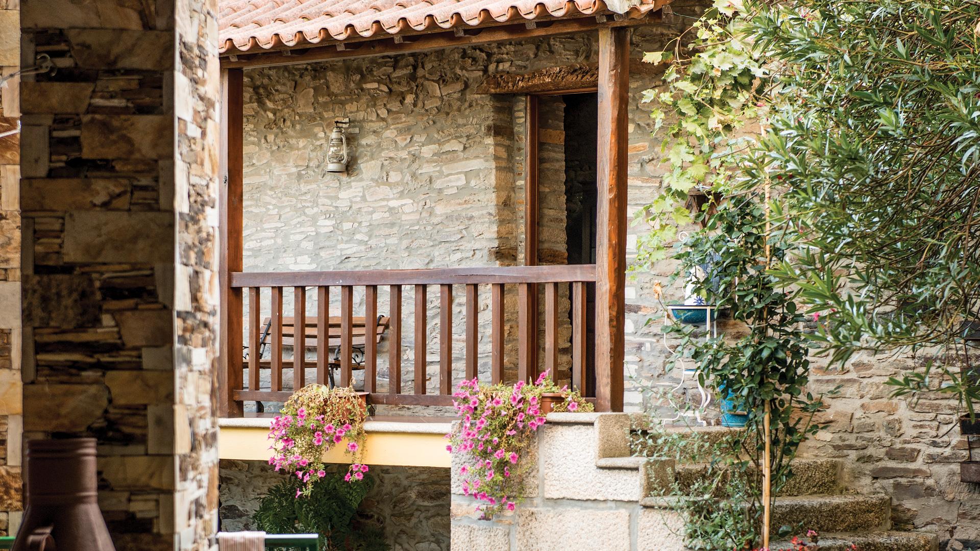 Entrada da Casa da Amoreira: alpendre com gradeamento de madeira e escadas de pedra.